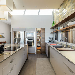 Mid-century modern open concept kitchen ideas - Example of a 1950s galley open concept kitchen design in San Francisco with stainless steel appliances, an undermount sink, flat-panel cabinets, white cabinets, multicolored backsplash and subway tile backsplash