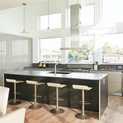 Huge trendy l-shaped light wood floor and brown floor open concept kitchen photo in Houston with an island, flat-panel cabinets, gray cabinets, a double-bowl sink, quartz countertops, green backsplash and stainless steel appliances