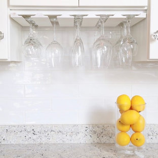 Photo of a medium sized coastal l-shaped kitchen in Other with flat-panel cabinets, white cabinets, granite worktops, white splashback, metro tiled splashback, stainless steel appliances, light hardwood flooring, an island and yellow worktops.
