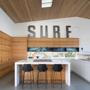 Idéer för att renovera ett maritimt vit vitt kök, med släta luckor, skåp i ljust trä, bänkskiva i kvarts, betonggolv, en köksö, grått golv, en undermonterad diskho, fönster som stänkskydd och integrerade vitvaror
