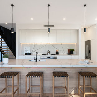 Inspiration for a contemporary l-shaped kitchen in Other with white cabinets, marble benchtops, marble splashback, stainless steel appliances, laminate floors, with island, an undermount sink, flat-panel cabinets, white splashback, brown floor and white benchtop.