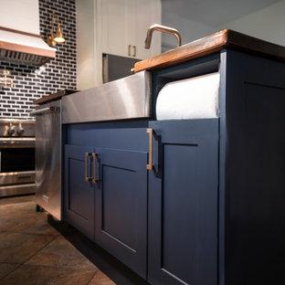 マイアミの広いコンテンポラリースタイルのおしゃれなキッチン (ドロップインシンク、シェーカースタイル扉のキャビネット、青いキャビネット、木材カウンター、青いキッチンパネル、レンガのキッチンパネル、シルバーの調理設備、テラコッタタイルの床、茶色い床、茶色いキッチンカウンター) の写真