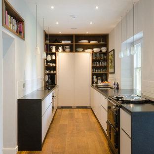 Idee per una piccola cucina ad U contemporanea chiusa con elettrodomestici neri e pavimento in legno massello medio