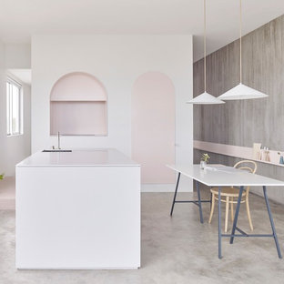 Inspiration for a scandinavian l-shaped eat-in kitchen in Sydney with an undermount sink, flat-panel cabinets, cement tiles, with island and grey floor.