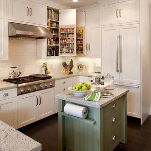 Foto på ett lantligt u-kök, med skåp i shakerstil, vita skåp, vitt stänkskydd, stänkskydd i tunnelbanekakel och integrerade vitvaror