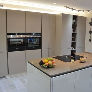 Photo of a medium sized contemporary galley kitchen/diner in Other with an integrated sink, recessed-panel cabinets, grey cabinets, integrated appliances, an island, granite worktops, white splashback, brick splashback, light hardwood flooring and grey floors.