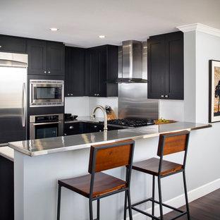 Immagine di una piccola cucina minimalista con lavello a doppia vasca, ante in stile shaker, ante nere, top in acciaio inossidabile, paraspruzzi a effetto metallico, paraspruzzi con piastrelle di metallo, elettrodomestici in acciaio inossidabile, parquet scuro e penisola
