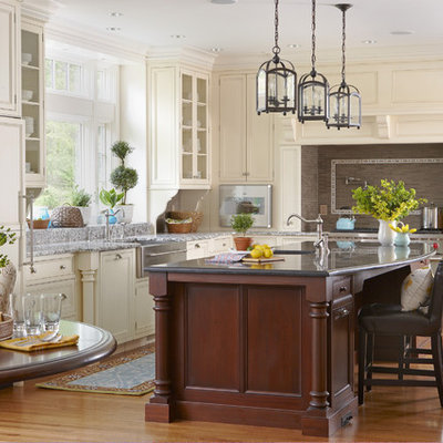 Inspiration for a large timeless l-shaped medium tone wood floor and brown floor eat-in kitchen remodel in Boston with recessed-panel cabinets, white cabinets, paneled appliances, a farmhouse sink, marble countertops, brown backsplash, mosaic tile backsplash and an island