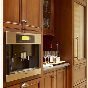 Large traditional kitchen pantry pictures - Example of a large classic single-wall medium tone wood floor and brown floor kitchen pantry design in Boston with recessed-panel cabinets, medium tone wood cabinets, marble countertops, paneled appliances and no island