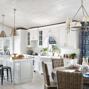 Inspiration for a mid-sized beach style single-wall open plan kitchen in Miami with a farmhouse sink, shaker cabinets, white cabinets, with island, quartz benchtops, multi-coloured splashback, glass tile splashback, stainless steel appliances and porcelain floors.