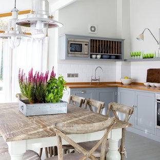 Maritime Küche mit Arbeitsplatte aus Holz, grauen Schränken, Schrankfronten im Shaker-Stil, Küchenrückwand in Weiß, Rückwand aus Keramikfliesen, Küchengeräten aus Edelstahl, Landhausspüle und gebeiztem Holzboden in Kent