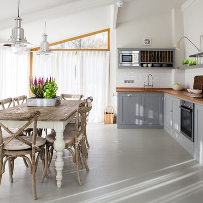 Cottage painted wood floor eat-in kitchen photo in Kent with shaker cabinets, gray cabinets, wood countertops, white backsplash, ceramic backsplash, stainless steel appliances, a farmhouse sink and no island
