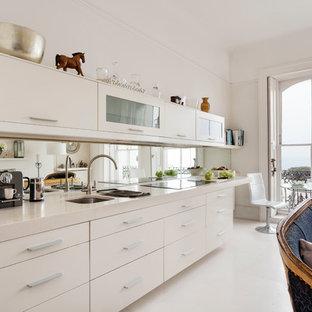 Immagine di una cucina lineare contemporanea chiusa e di medie dimensioni con lavello a doppia vasca, ante lisce, ante bianche, paraspruzzi a specchio e pavimento bianco