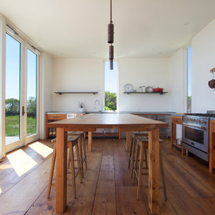 Inspiration for a large modern l-shaped kitchen/diner in Providence with a belfast sink, open cabinets, medium wood cabinets, zinc worktops, stainless steel appliances, medium hardwood flooring and an island.
