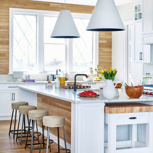 Photo of a beach style kitchen in New York with shaker cabinets, white cabinets, timber splashback, stainless steel appliances, white benchtop, beige splashback, light hardwood floors, multiple islands, beige floor and marble benchtops.