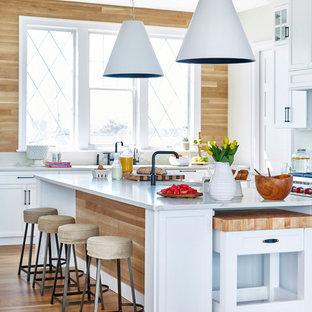 Cette image montre une cuisine marine avec un placard à porte shaker, des portes de placard blanches, une crédence en bois, un électroménager en acier inoxydable, un plan de travail blanc, une crédence beige, un sol en bois clair, 2 îlots, un sol beige et un plan de travail en marbre.