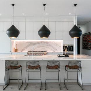 タンパの大きいコンテンポラリースタイルのおしゃれなキッチン (アンダーカウンターシンク、フラットパネル扉のキャビネット、白いキャビネット、クオーツストーンカウンター、マルチカラーのキッチンパネル、パネルと同色の調理設備、無垢フローリング、茶色い床、石スラブのキッチンパネル、白いキッチンカウンター) の写真