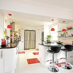 Idées déco pour une cuisine américaine contemporaine en U avec un évier encastré, un placard à porte plane, des portes de placard blanches, un électroménager en acier inoxydable, un plan de travail en quartz, une crédence en feuille de verre et un sol multicolore.
