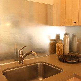 シアトルの小さいエクレクティックスタイルのおしゃれなキッチン (アンダーカウンターシンク、ガラス扉のキャビネット、淡色木目調キャビネット、珪岩カウンター、メタリックのキッチンパネル、メタルタイルのキッチンパネル、白い調理設備、竹フローリング) の写真