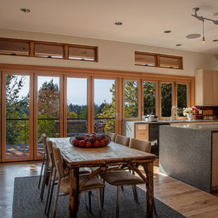 Mid-sized contemporary open concept kitchen photos - Inspiration for a mid-sized contemporary u-shaped light wood floor open concept kitchen remodel in Seattle with an undermount sink, flat-panel cabinets, light wood cabinets, recycled glass countertops, red backsplash, glass tile backsplash, black appliances and an island
