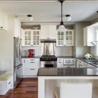 Imagen de cocina en U, de estilo americano, con encimera de vidrio reciclado, fregadero de un seno, armarios tipo vitrina, puertas de armario blancas, salpicadero blanco, salpicadero de azulejos tipo metro y electrodomésticos de acero inoxidable