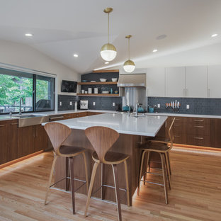 Design ideas for a large midcentury eat-in kitchen in Seattle with a farmhouse sink, flat-panel cabinets, white cabinets, quartz benchtops, blue splashback, ceramic splashback, stainless steel appliances, medium hardwood floors, with island and white benchtop.