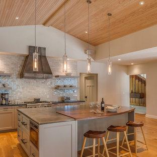 Offene, Geräumige Moderne Küche in L-Form mit Schrankfronten mit vertiefter Füllung, grauen Schränken, Zink-Arbeitsplatte, Küchenrückwand in Grau, Rückwand aus Metrofliesen, Küchengeräten aus Edelstahl, braunem Holzboden und Kücheninsel in Portland Maine
