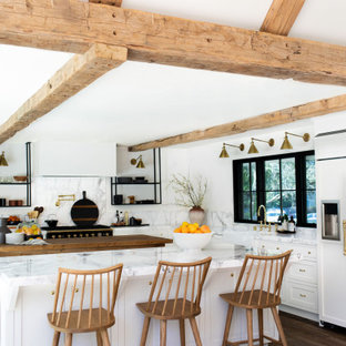 Inspiration for a country l-shaped kitchen in San Francisco with a farmhouse sink, shaker cabinets, white cabinets, black appliances, dark hardwood floors, multiple islands, brown floor and white benchtop.