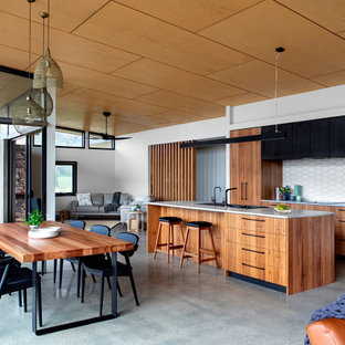 Photo of a mid-sized contemporary galley open plan kitchen in Melbourne with concrete floors, grey floor, a drop-in sink, flat-panel cabinets, medium wood cabinets, white splashback, stainless steel appliances, with island and grey benchtop.