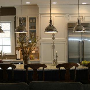 Idéer för mellanstora vintage kök, med rostfria vitvaror, vita skåp, granitbänkskiva, brunt stänkskydd, stänkskydd i glaskakel, en undermonterad diskho, skåp i shakerstil, mellanmörkt trägolv och en köksö