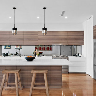 This is an example of a mid-sized contemporary open plan kitchen in Melbourne with a double-bowl sink, quartz benchtops, mirror splashback, stainless steel appliances, with island, white benchtop, flat-panel cabinets, dark wood cabinets and medium hardwood floors.