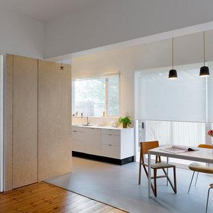 Zweizeilige, Kleine Nordische Wohnküche ohne Insel mit Einbauwaschbecken, weißen Schränken, Quarzit-Arbeitsplatte, Küchenrückwand in Schwarz, Rückwand aus Spiegelfliesen, Küchengeräten aus Edelstahl und Linoleum in Melbourne