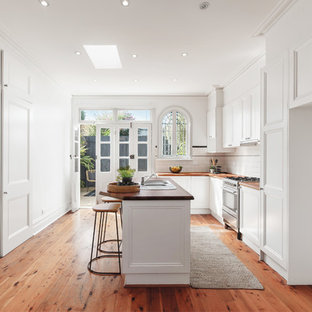 This is an example of a country u-shaped kitchen in Melbourne with a drop-in sink, recessed-panel cabinets, white cabinets, wood benchtops, white splashback, subway tile splashback, stainless steel appliances, medium hardwood floors, with island, brown floor and brown benchtop.