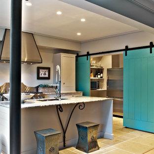 Пример оригинального дизайна: маленькая линейная кухня в стиле модернизм с обеденным столом, врезной раковиной, фасадами с декоративным кантом, белыми фасадами, столешницей из оникса, фартуком цвета металлик, фартуком из металлической плитки, техникой из нержавеющей стали, бетонным полом и островом