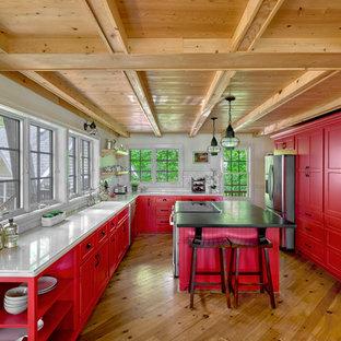 シカゴの中サイズのビーチスタイルのおしゃれなアイランドキッチン (落し込みパネル扉のキャビネット、赤いキャビネット、クオーツストーンカウンター、白いキッチンパネル、シルバーの調理設備の、白いキッチンカウンター、サブウェイタイルのキッチンパネル、無垢フローリング) の写真