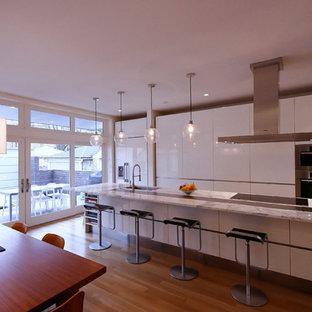 Idées déco pour une cuisine américaine parallèle moderne de taille moyenne avec un évier encastré, un placard à porte plane, des portes de placard blanches, un plan de travail en marbre, un sol en bois clair et un îlot central.