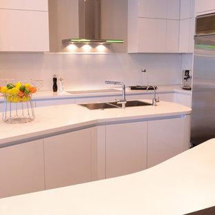 Diseño de cocina en U, minimalista, grande, abierta, con fregadero encastrado, armarios con paneles lisos, puertas de armario blancas, encimera de granito, salpicadero blanco, electrodomésticos de acero inoxidable, suelo de baldosas de cerámica y una isla