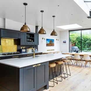 ロンドンのトランジショナルスタイルのおしゃれなキッチン (エプロンフロントシンク、シェーカースタイル扉のキャビネット、黒いキャビネット、黄色いキッチンパネル、シルバーの調理設備の、無垢フローリング、茶色い床、白いキッチンカウンター) の写真