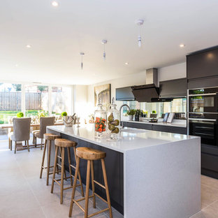 This is an example of a medium sized contemporary kitchen/diner in Buckinghamshire with flat-panel cabinets, marble worktops, black appliances, ceramic flooring, an island, grey worktops, a submerged sink, black cabinets, window splashback and grey floors.