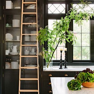 Victorian kitchen photos - Kitchen - victorian dark wood floor kitchen idea in Portland with glass-front cabinets, black cabinets, marble countertops and an island