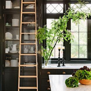 ポートランドのヴィクトリアン調のおしゃれなアイランドキッチン (ガラス扉のキャビネット、黒いキャビネット、大理石カウンター、濃色無垢フローリング) の写真