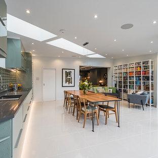 Exempel på ett mellanstort modernt linjärt kök och matrum, med en undermonterad diskho, släta luckor, gröna skåp, stänkskydd med metallisk yta, stänkskydd i tegel, integrerade vitvaror, klinkergolv i keramik och beiget golv