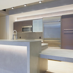This is an example of a mid-sized contemporary galley kitchen in Miami with flat-panel cabinets, brown cabinets, concrete benchtops, grey splashback, stainless steel appliances, light hardwood floors and a peninsula.