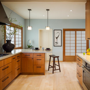 This is an example of an asian u-shaped kitchen in San Francisco with flat-panel cabinets, medium wood cabinets, green splashback, subway tile splashback, stainless steel appliances, light hardwood floors, a peninsula, beige floor and beige benchtop.