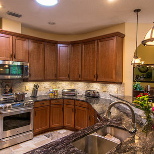Photo of a medium sized traditional u-shaped kitchen/diner in Tampa with a submerged sink, shaker cabinets, medium wood cabinets, granite worktops, grey splashback, mosaic tiled splashback, stainless steel appliances and travertine flooring.