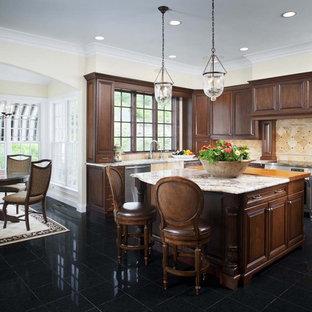 Esempio di una cucina abitabile chic con ante con bugna sagomata, ante in legno scuro, paraspruzzi beige, elettrodomestici in acciaio inossidabile e pavimento nero