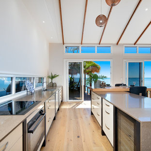 Design ideas for a beach style galley kitchen in Brisbane with an undermount sink, flat-panel cabinets, white cabinets, light hardwood floors, with island, beige floor and window splashback.