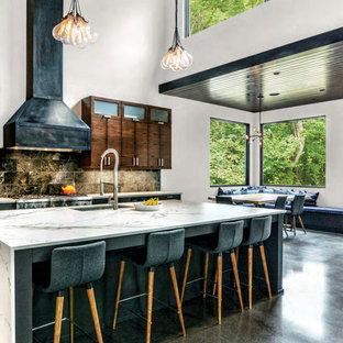 Cette image montre une cuisine ouverte parallèle urbaine avec un évier encastré, un placard à porte plane, des portes de placard en bois sombre, une crédence noire, un électroménager en acier inoxydable, béton au sol, un îlot central et un sol gris.