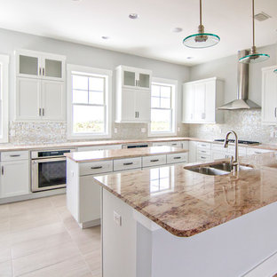Large beach style u-shaped open plan kitchen in Jacksonville with a double-bowl sink, shaker cabinets, white cabinets, granite benchtops, white splashback, glass tile splashback, stainless steel appliances, porcelain floors, with island, beige floor and brown benchtop.
