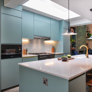 This is an example of a medium sized contemporary galley open plan kitchen in London with a built-in sink, recessed-panel cabinets, blue cabinets, quartz worktops, white splashback, marble splashback, light hardwood flooring, white floors, integrated appliances, an island and white worktops.